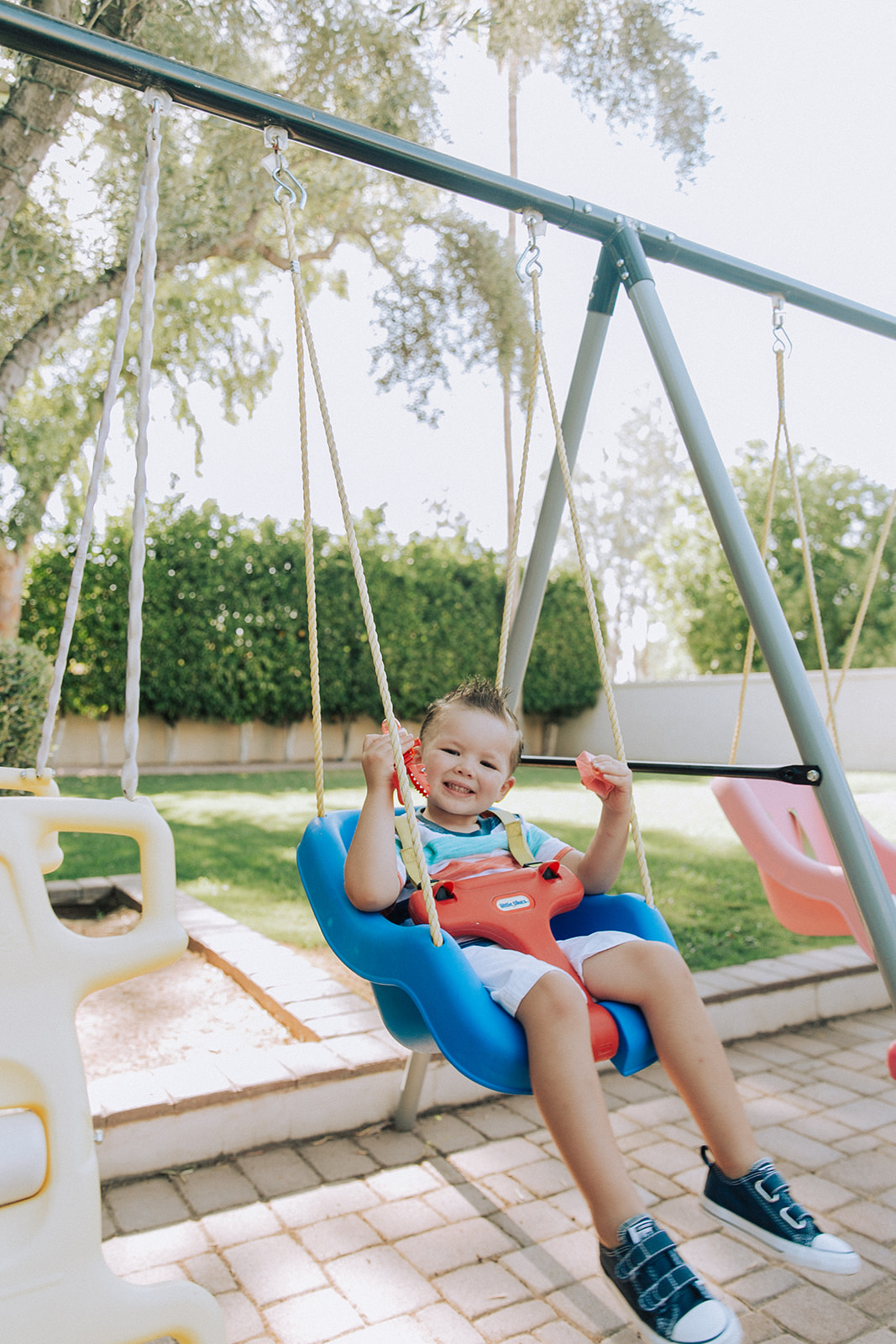 Diego smiling while swinging on a swing.