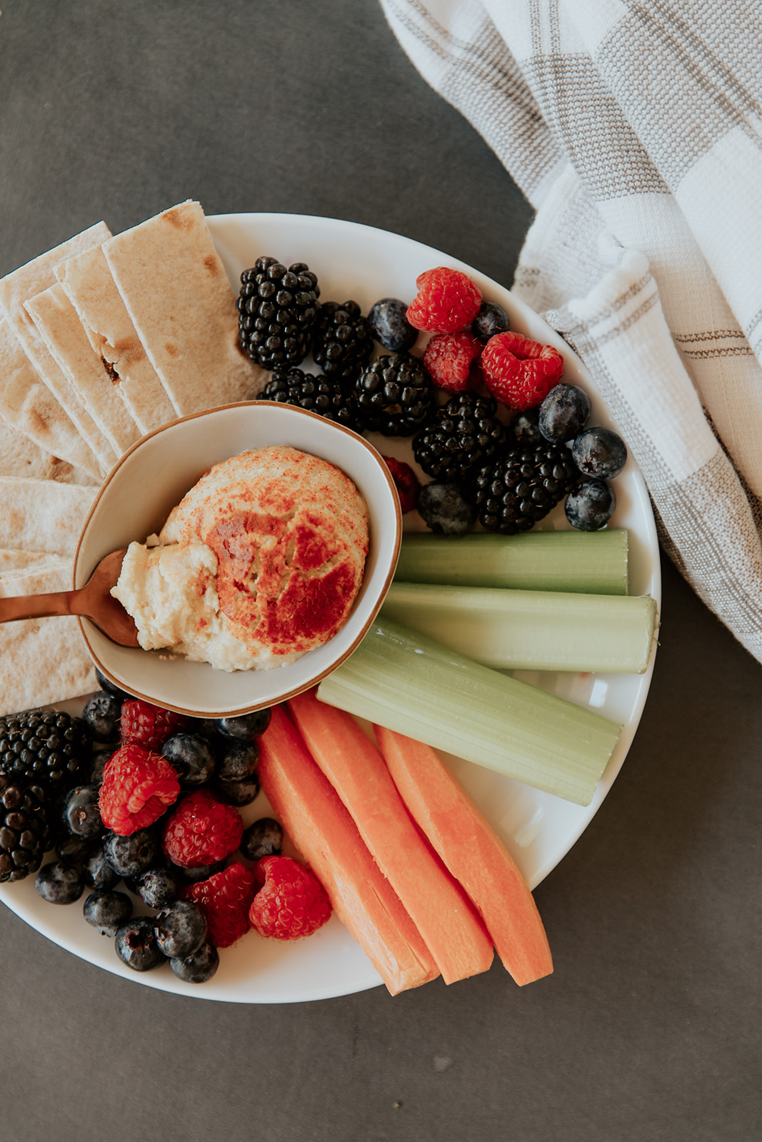 Hummus, veggies and berries on a plate.